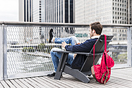 USA, New York, Businessan in Manhattan using smart phone and earphones - UUF09213