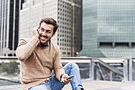 USA, New York, Businessan in Manhattan using smart phone and headphones - UUF09219