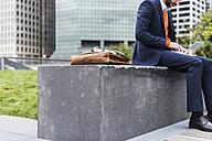 USA, New York City, Businessman working outdoor sitting on bench - UUF09228