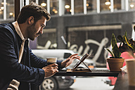 USA, New York City, Businessman sitting in coffee shop, using digital tablet - UUF09231