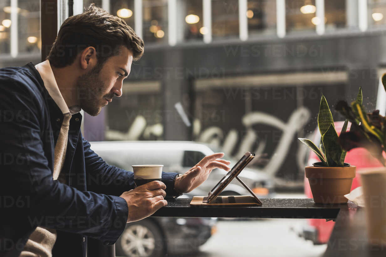 USA, New York City, Businessman sitting in coffee shop, using digital tablet - UUF09231 - Uwe Umstätter/Westend61