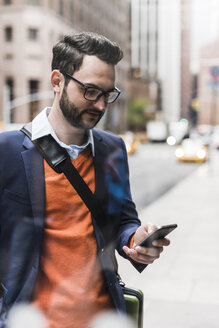 USA, New York City, Businessman using smart phone - UUF09234