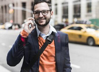 USA, New York City, Businessman using smart phone - UUF09237