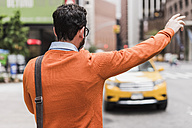 USA, New York City, Businessman hailing cab - UUF09240