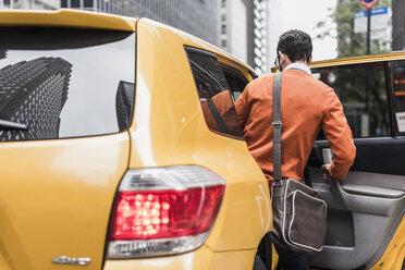 USA, New York City, Businessman entering cab - UUF09246