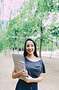 Smiling young woman holding a laptop and a notebook outdoors - GEMF01254