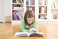 Little girl lying on the floor reading a book - LVF05601