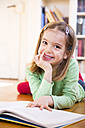 Portrait of smiling little girl lying on the floor with book - LVF05604