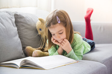 Little girl lying on couch watching  book - LVF05607
