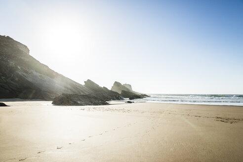 Portugal, Alentejo, Rocks and footprints at Zambujeira do Mar beach - CHPF00323