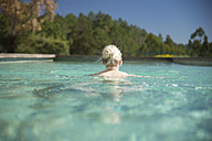 Woman swimming in pool, rear view - CHPF00329