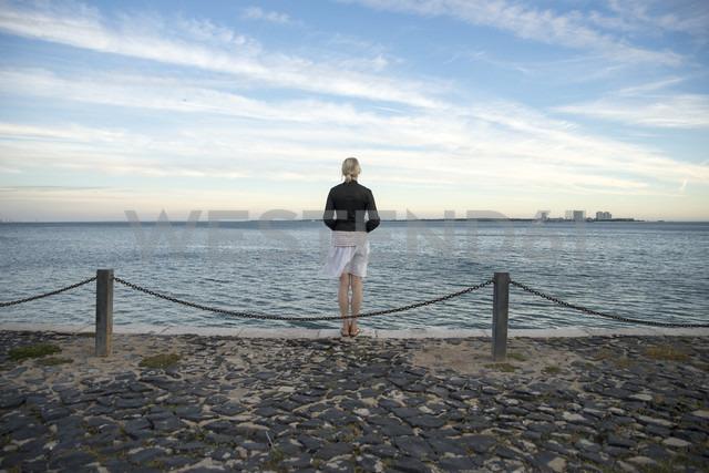 Portugal, Setubal, Woman standing at the sea looking at Troia penninsula - CHPF00344