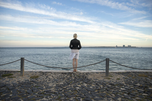 Portugal, Setubal, Woman standing at the sea looking at Troia penninsula - CHPF00344