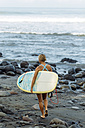 Indonesia, Bali, woman carrying surfboard at the sea - KNTF00576