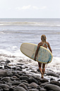 Indonesia, Bali, woman carrying surfboard at the sea - KNTF00582