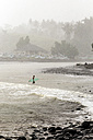 Indonesia, Bali, surfer carrying surfboards in the sea - KNTF00585