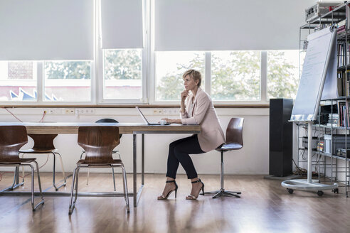 Businesswoman using laptop in modern conference room - RIBF00587