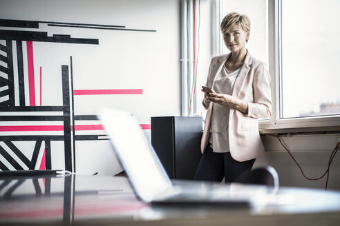 Confident businesswoman with cell phone standing in modern office - RIBF00602