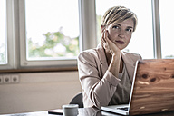 Businesswoman with laptop in conference room thinking - RIBF00605