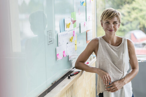 Smiling businesswoman with adhesive notes at whiteboard in modern office - RIBF00614