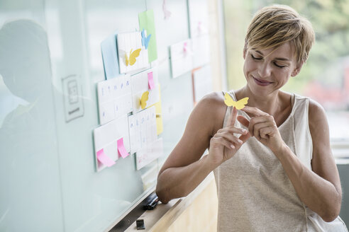 Smiling businesswoman with adhesive notes at whiteboard in modern office - RIBF00617