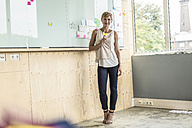 Businesswoman with adhesive notes at whiteboard in modern office - RIBF00620