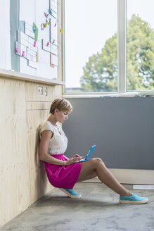 Businesswoman using mini tablet at wooden wall with board - RIBF00629