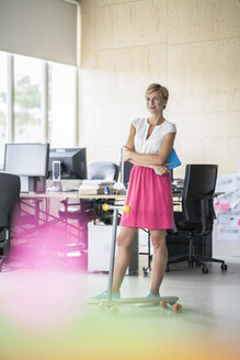 Woman standing in creative office - RIBF00632