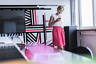 Woman in modern office looking at smartphone - RIBF00641