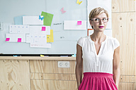 Businesswoman in front of whiteboard in modern office - RIBF00644