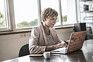 Businesswoman using laptop in conference room - RIBF00647