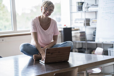 Smiling woman sitting on table using laptop - RIBF00659