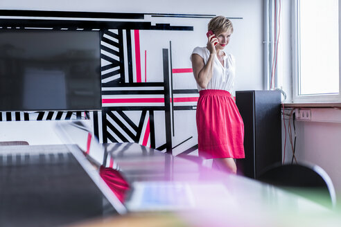 Woman in modern office on cell phone - RIBF00662