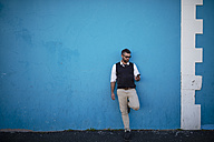 Man leaning against blue wall looking on cell phone - ZEF11628