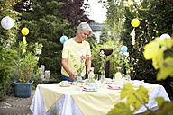 Mature woman decoration garden table for birthday party - MFRF00744