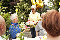 Mature woman serving birthday cake - MFRF00768