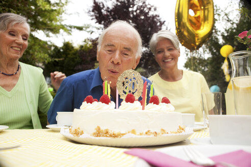 Senior man blowing candle on 80th birthday cake - MFRF00771