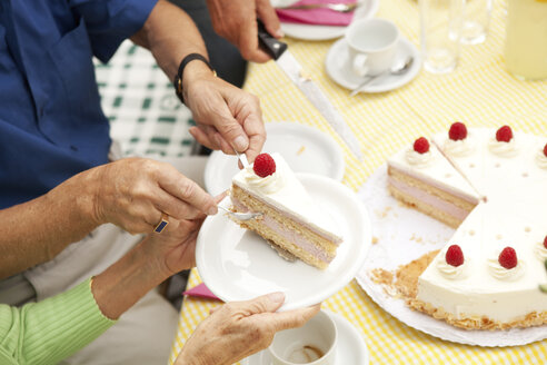 Hands putting cream cake on plates - MFRF00774