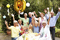 Extended family and friends having birthday party in garden - MFRF00810