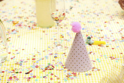 Party hat and party blower on table with confetti - MFRF00813