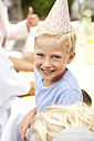 Blond boy wearing party hat at birthday party - MFRF00819