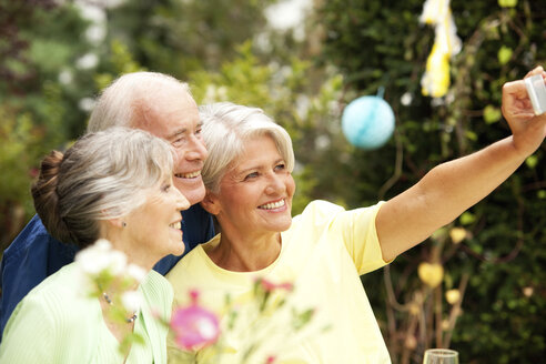 Senior man taking selfie with guests - MFRF00822