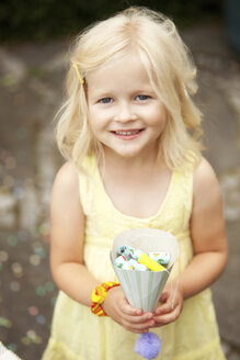 Little girl holding party hat filled with party blowouts - MFRF00828