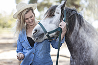 Smiling woman with horse on horse farm - ZEF11742