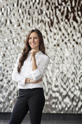 Portrait of confident businesswoman in front of rippled wall - PESF00363