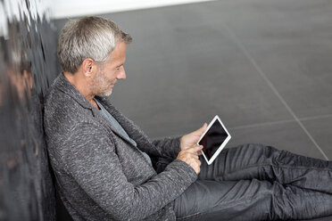 Businessman sitting at wall using tablet - PESF00366