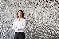 Portrait of confident businesswoman in front of rippled wall - PESF00378