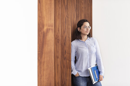Young woman at wooden wall holding folders - PESF00384