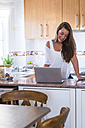 Smiling young woman using laptop in kitchen - SIPF01105