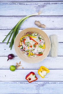 Bowl of glass noodle salad with vegetables and ingredients on wood - LVF05609